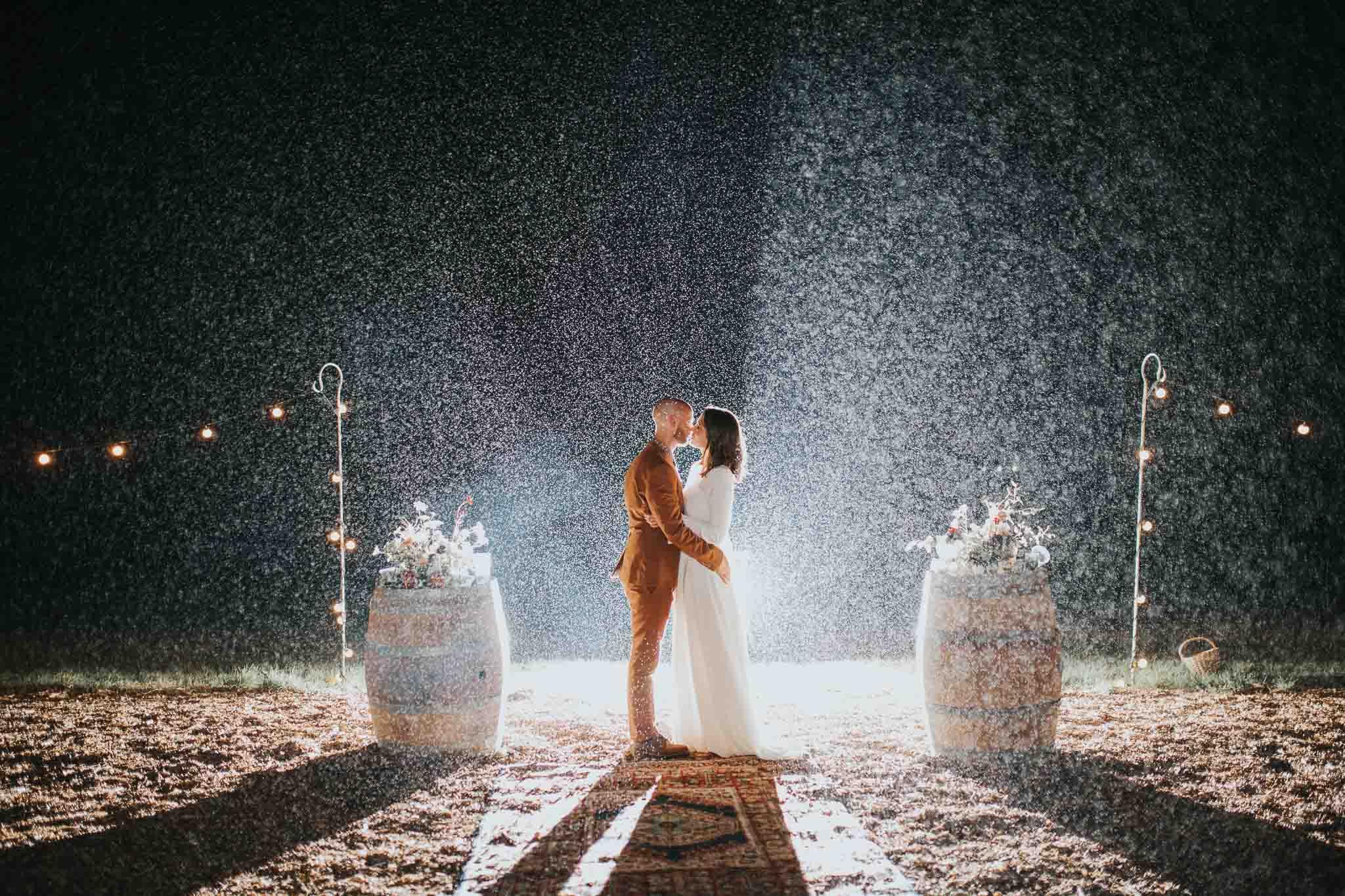 bride and groom kissing in the rain pennard hill farm