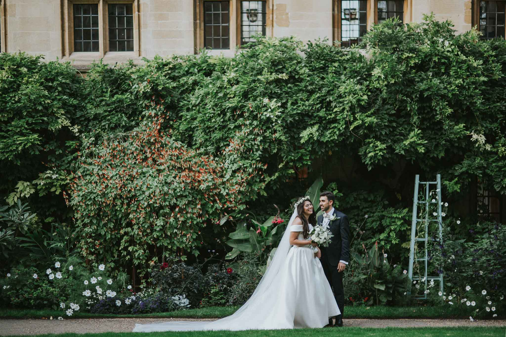 bride and groom walking in the garden of Bailliol College in Oxford