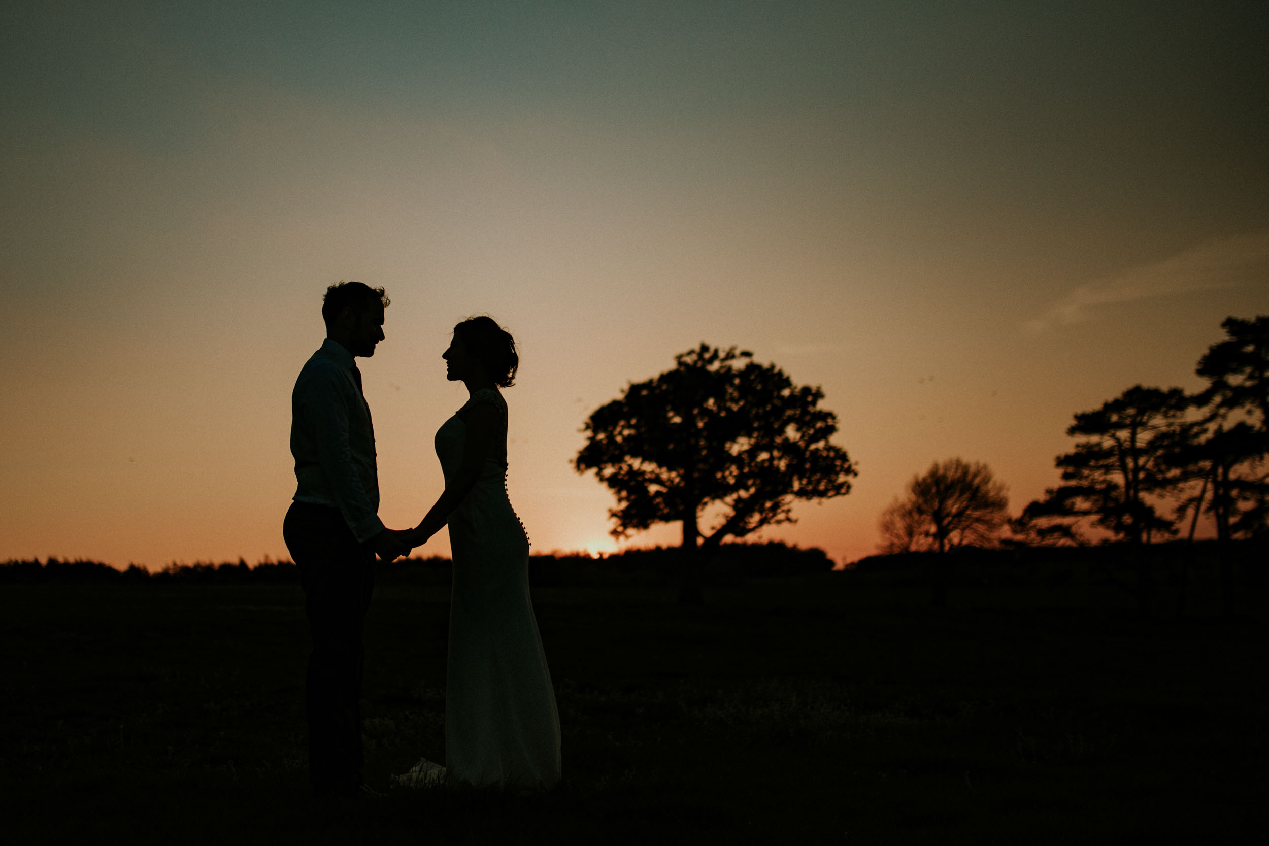 couple watching sunset silhouette