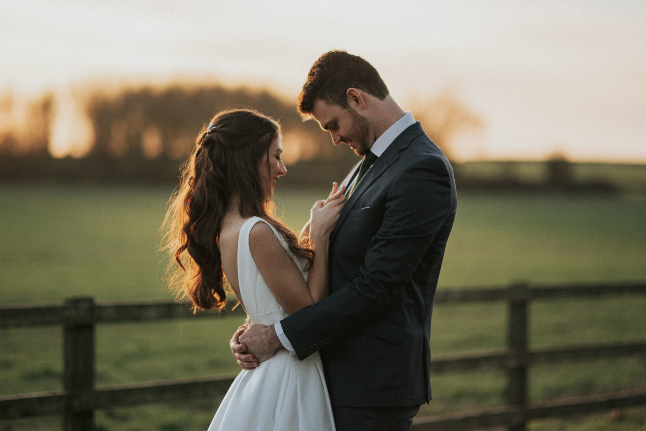 bride and groom cuddling on the fields in Stratton Audley, Oxfordshire